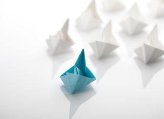 Ein blaues Schiff führt viele weiße Schiffe